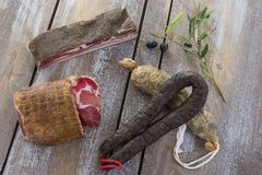 Several variety of traditional Corsican charcuterie with an olive branch and black olives on wooden background Royalty Free Stock Images