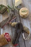 Several variety of traditional Corsican charcuterie with an olive branch and black olives on wooden background Royalty Free Stock Photo