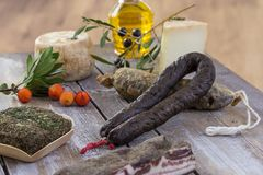 Several variety of traditional Corsican charcuterie with an olive branch and black olives on wooden background. Several variety of traditional Corsican Royalty Free Stock Photo