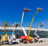 Several various self propelled articulated boom lift. Several various mobile aerial work platform - self propelled hydraulic articulated boom lift against the Royalty Free Stock Images