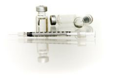 Several vials with hypodermic needle. Three vials of liquid and a horizontal syringe, isolated against white royalty free stock images