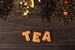Several views of tea and a cookie inscription on a wooden background royalty free stock photos