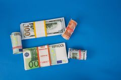 several wads of money of different currencies on a blue background stock image