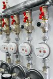 Several water meters. Measurement and brass distributor with red valves of water flow. Stock Images