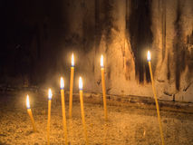 Several wax candles lighted in a dark room. Picture of the several wax candles lighted in a dark room in a church. Candles lighting against background of the royalty free stock photos