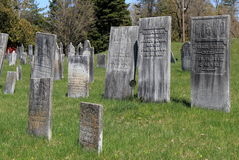 Several weathered headstones in the Old Revolutionary Cemetery, Salem, New York, 2016. Several old, weathered headstones set over acres of grassy knolls, Old royalty free stock photos