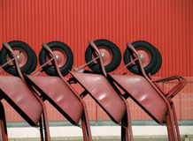 Several wheelbarrows in geometric position. With as background the red wall of the wharehouse Stock Photos
