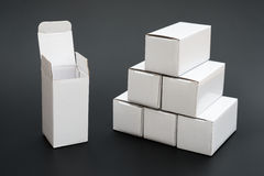 Several white boxes with one opened and ther other closed Royalty Free Stock Images