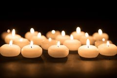 Several white candles with selective focus at a black background Stock Image