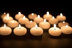 Several white candles with selective focus at a black background Stock Images