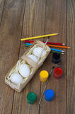 Several white chicken eggs, paint, brushes and pencils. Chicken white eggs, paint, brushes and pencils. They lie on a wooden table in a wicker basket. Prepared Stock Photo