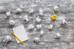 Several white crumpled paper balls with one colorful yellow and. Notepad and pencil. In search of inspiration and creativity. Metaphor for good idea stock photo