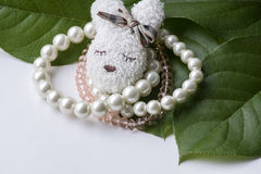 Several white and pink bracelets with brooch. On the green leaves and white background Stock Images