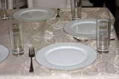 Several white plates with napkins, wine glasses, forks and knives on a table covered with a silk tablecloth. Table setting royalty free stock photos