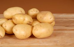 Several white potatoes piled on a cutting board Stock Images