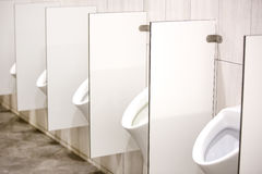 Several white urinals Stock Images