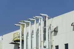 Several white ventilation vents are located next to the building.  royalty free stock images
