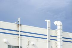 Several white ventilation vents are located next to the building.  stock image