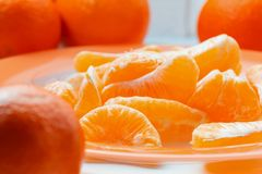Several whole and peeled ripe tangerines on a orange plate stock image