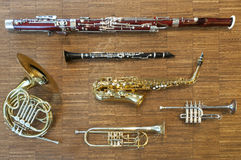 Several wind instruments. Laying on a wooden floor. trumpet, horn, saxophone, clarinet, flute,  bassoon, curtal Stock Photo