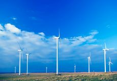 Several wind turbines. Copy space, rural background, nine objects. Nice blue sky, in the background horizon over the Baltic sea. Wind turbines situated on the Stock Images