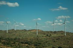 Several wind turbines over hilly landscape. Several wind turbines for electric power generation over green hilly landscape with rocks, in a sunny day at Sortelha stock images