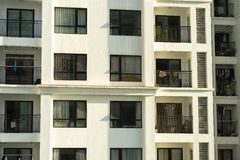 Several windows in a row on facade of urban apartment building front view in Hanoi, Vietnam.  Royalty Free Stock Image