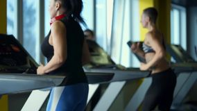 Several women are actively running on a treadmill in the fitness club. Several women are actively running on the treadmill in the fitness club. Athletes are stock video