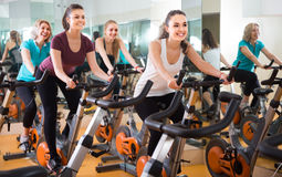 Several women of different age training on exercise bikes. Together stock images