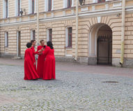 Several women in identical red dresses talk to each other gathered in a circle. Saint-Petersburg. Summer 2017 royalty free stock photo