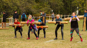 Several women in the jump with a  log. Royalty Free Stock Photo