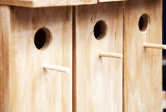 Several wooden birdhouses in a row background. A few wood bird houses for sale Stock Photo
