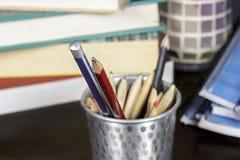 Several wooden pencils into a metal pencil case on a desk Stock Photos
