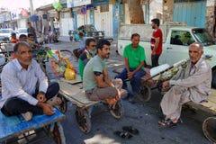 Several workers Bazaar sit on platforms wheelbarrows during rece Stock Photos