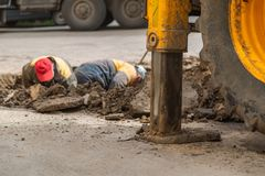 Several workers in overalls, digging a hole for troubleshooting. Several workers in overalls, digging a hole for troubleshooting plumbing royalty free stock image