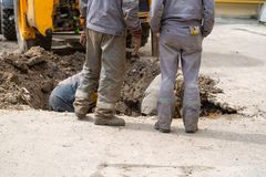 Several workers in overalls, digging a hole for troubleshooting. Several workers in overalls, digging a hole for troubleshooting plumbing royalty free stock images