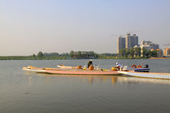 Several workers were putting in order dragon boats in water, in Royalty Free Stock Photography