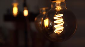 Several yellow bright vintage bulbs swinging in the black background. Concept of light and dark, idea, electricity at. A modern home stock video footage