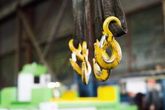 Several yellow cargo hooks hanging on dirty, oiled textile slings. Royalty Free Stock Photo