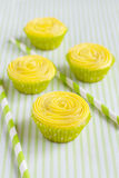 Several yellow cupcakes and drinking straws Royalty Free Stock Photography