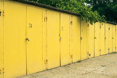 Several yellow numbered car garage outdoors Stock Image