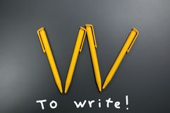 Several yellow plastic pens in the form of a letter W on a gray background and calls to write.  stock photography