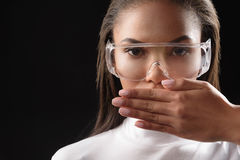Severe african woman gesturing for silence. No talk. Serious young mulatto girl is covering her mouth by hand. She is looking at camera confidently. Isolated and Stock Photo
