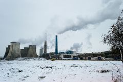Severe air pollution from several coal burning power plants, with tall chimneys releasing fumes at sunset. In a cold Winter day - Bucharest, Romania stock photo
