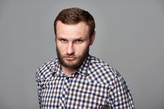 Severe bearded man in checkered shirt. Portrait of severe bearded man in checkered shirt standing on gray background staring at camera Royalty Free Stock Image