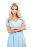 Severe blonde model in blue dress posing crossed arms Royalty Free Stock Photos