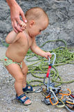 Severe climber. Photo son of pair climbers. When daddy boy climbing on rocks, he played with carbines and other climbing gadgets Royalty Free Stock Photography