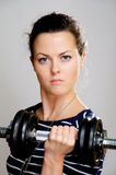 Severe girl with dumbbells Stock Photos