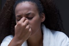 Severe headache that keeps her awake at night. Close-up, night portrait of a young woman with closed eyes and painful expression of her face Stock Image