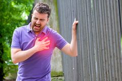 Severe heartache.Man pressing on chest with painful expression fist aid needed royalty free stock photos